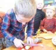 Pašas maizītes gatavas - jāsagatavo, ko virsū likt. Sešgadnieks Arvis griež gurķi. Darbiņš jādara rūpīgi un uzmanīgi!