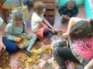 Lielie bērni darbojas ar koku lapām, kas šogad bija īpaši skaistas